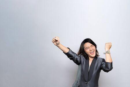 Foto de Happy woman make winning gesture isolated over white background - Imagen libre de derechos