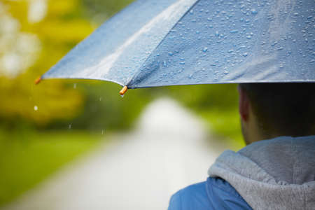 Young man with umbrella - selective focus on drop