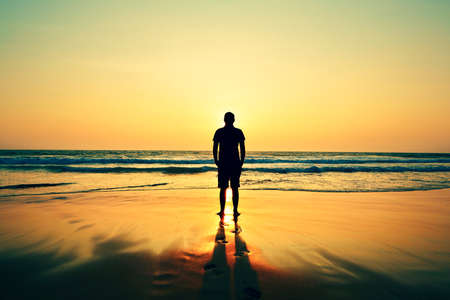 Photo for Silhouette of young man on the beach at sunset.  - Royalty Free Image
