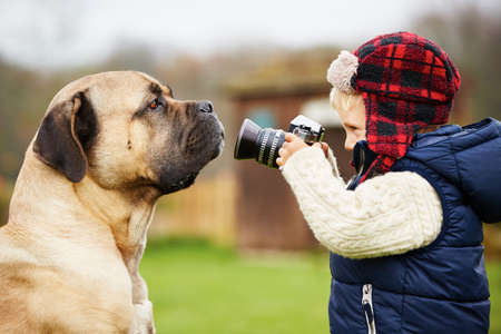 Photo for Little boy with camera is shooting his dog - Royalty Free Image