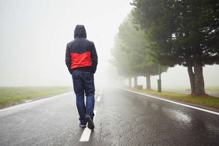 Photo for Lonely man is walking in mysterious fog - Royalty Free Image