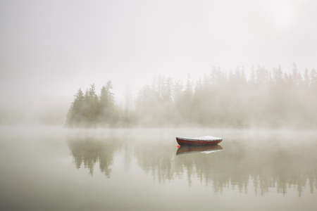 Boat on the lake at morning fog.