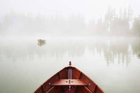 Boats on the lake at morning fog.
