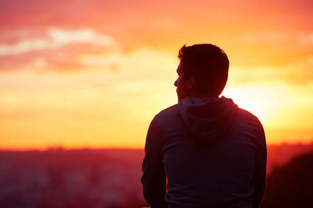 Photo for Young man is looking at the sunrise. - Royalty Free Image