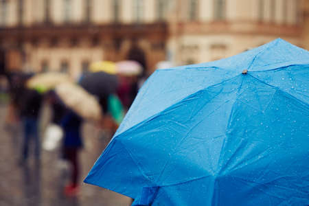 People with umbrellas in rain on the street - selective focus