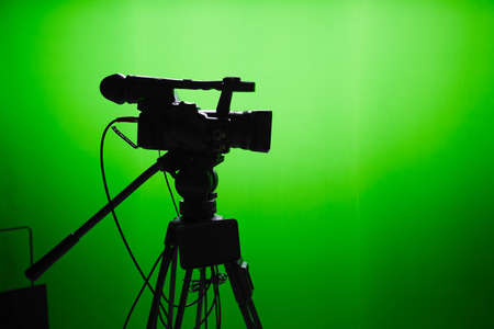 Photo for Silhouette of digital video camera in front of the green screen - Royalty Free Image