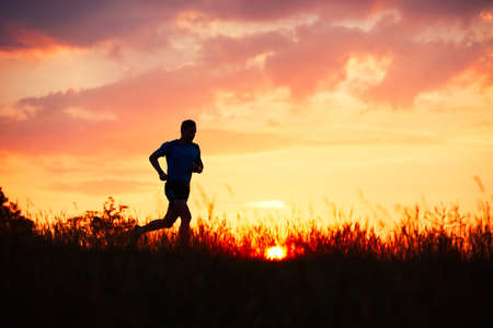 Photo pour Silhouette of runner. Outdoor cross-country running. Athletic young man is running in the nature during golden sunset. - image libre de droit