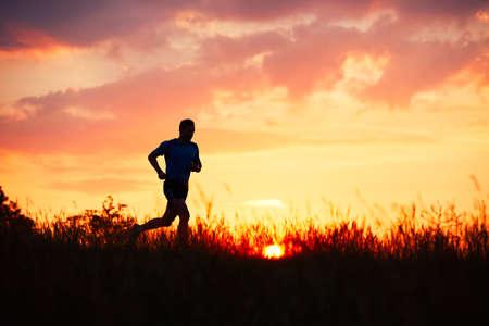 Foto de Silhouette of runner. Outdoor cross-country running. Athletic young man is running in the nature during golden sunset. - Imagen libre de derechos