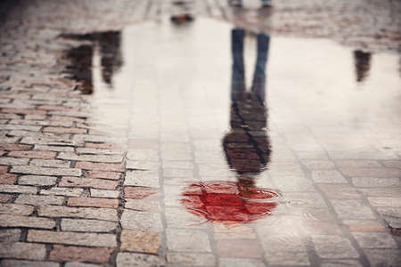Photo pour Rainy day. Reflection of young man with red umbrella in puddle on the city street during rain. - image libre de droit