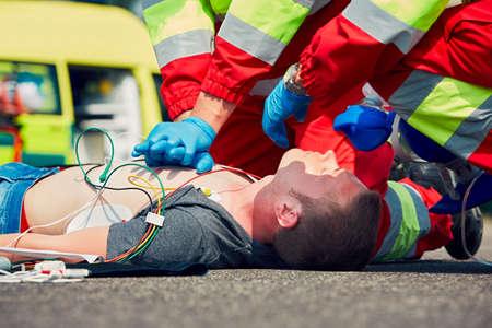 Foto de Cardiopulmonary resuscitation. Rescue team (doctor and a paramedic) resuscitating the man on the street. - Imagen libre de derechos