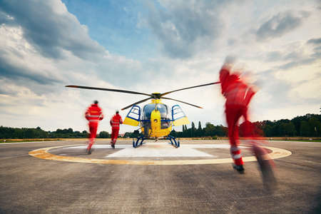 Foto de Alarm for the air rescue service. Team of rescuers (paramedic, doctor and pilot) running to the helicopter on the heliport. - Imagen libre de derechos
