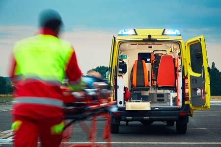 Foto de Emergency medical service. Paramedic is pulling stretcher with patient to the ambulance car. - Imagen libre de derechos