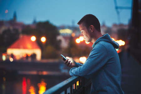Photo pour Alone in the night city with mobile phone. Handsome dreamy man reading message (or looking on the video) on his smartphone. - image libre de droit