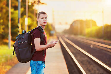 Photo pour Traveler is late at the train station. Young man with backpack missed the train and waiting for next. - image libre de droit