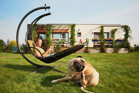 Foto de Young man reading book in the swing and large dog resting on the garden of the modern family house. - Imagen libre de derechos