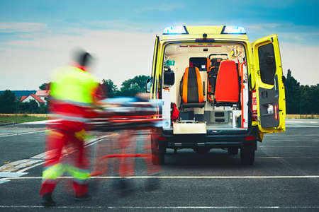 Photo for Emergency medical service. Paramedic is pulling stretcher with patient to the ambulance car. - Royalty Free Image