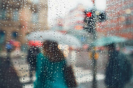 Gloomy day in the city. People in heavy rain. Selective focus on the raindrops. Prague, Czech Republic.