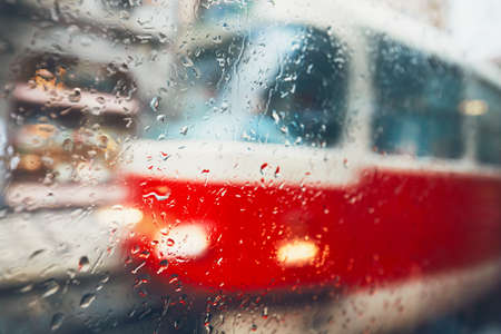 Gloomy day in the city. Tram on the street in rain. Selective focus on the raindrops on the window. Prague, Czech Republic.