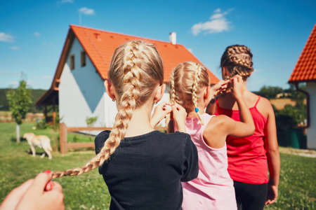 Photo pour Girls each to other making hair braids of the little girl on the garden in the countryside. - image libre de droit