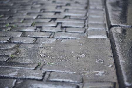 Puddle on road in rain. Full frame shot of cobblestone street.