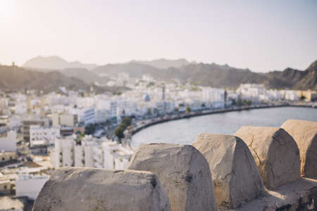 Muscat city at sunset. Selective focus on details of fort. Sultanate of Oman.