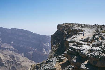 Grand Canyon of Oman. Tourist walking on the edge of cliff. Mountain range Jebel Akhdar.
