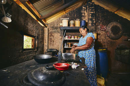 Photo pour Rural woman preparing food in traditional home kitchen. Domestic life in Sri Lanka. - image libre de droit