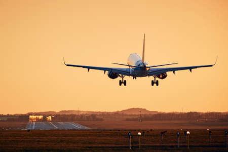 Foto de Airplane landing on runway. Traffic at airport at golden sunset. - Imagen libre de derechos
