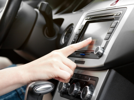 Photo for finger on dashboard with gps panel and tv dvd audio system - Royalty Free Image