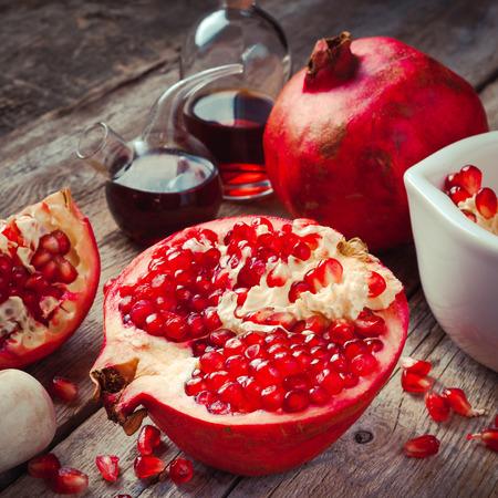 Photo pour Pomegranate and bottles of essence or tincture on wooden rustic table - image libre de droit