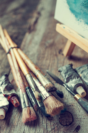 Photo for Artistic paintbrushes, tubes of oil paint, palette knife and easel with oil painting on old wooden desk. - Royalty Free Image
