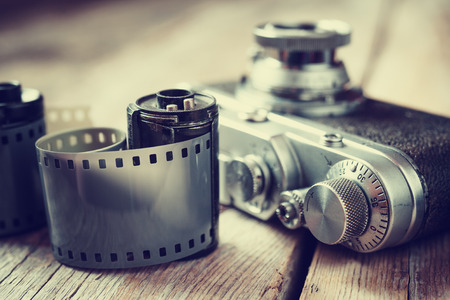 Photo for Old photo film rolls, cassette and retro camera, selective focus. Vintage stylized. - Royalty Free Image