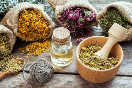 Photo for Healing herbs in hessian bags, mortar with chamomile and essential oil on wooden table, herbal medicine. - Royalty Free Image