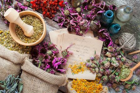 Foto de Healing herbs in hessian bags, wooden mortar, bottles with tincture, herbal medicine. Top view. - Imagen libre de derechos