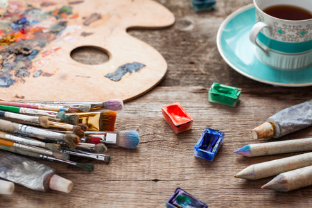 Photo for Paintbrushes, artist palette, pencils, coffee cup, watercolor and oil paints on desk in painter studio. - Royalty Free Image