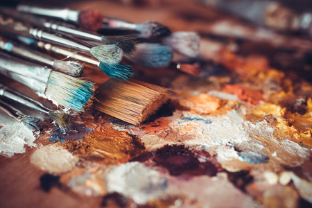 Photo for Paintbrushes closeup, artist palette and multicolor paint stains - Royalty Free Image