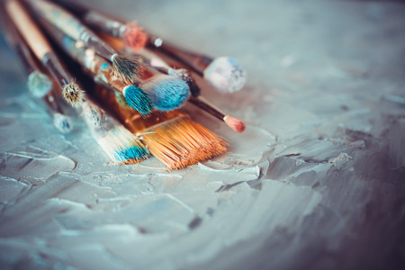 Foto de Paintbrushes on artist canvas covered  with oil paints - Imagen libre de derechos