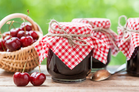 Foto de Jars of jam and basket with cherry. - Imagen libre de derechos