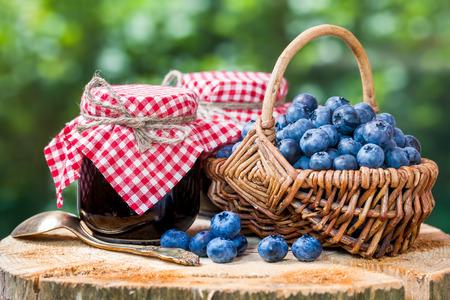 Foto de Basket with ripe blueberries and two jars of jam - Imagen libre de derechos
