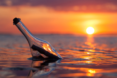 Foto de Bottle with a message in the sea at sunset - Imagen libre de derechos
