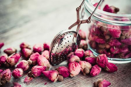 Photo pour Rose buds tea, tea infuser and glass jar. Selective focus. - image libre de droit