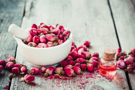 Photo pour Mortar with rose buds and essential roses oil. Selective focus. - image libre de droit