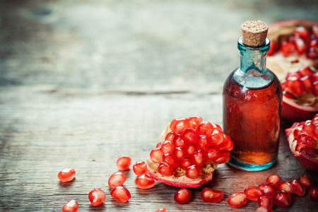 Photo pour Pomegranate tincture or  juice and red ripe garnet fruit with seeds on wooden table. Selective focus. - image libre de droit