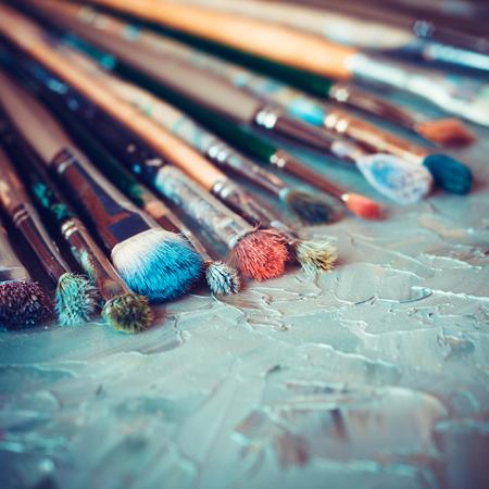Photo pour Artistic paintbrushes on artist canvas covered with oil paints - image libre de droit