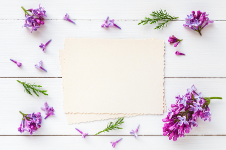 Photo for Old empty photo for the inside and frame of fresh lilac flowers on white wooden background. Flat lay, top view. - Royalty Free Image