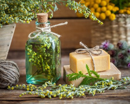 Photo for Bottle of tarragon tincture, healthy herbs and bars of homemade soap. Herbal medicine and natural care products. - Royalty Free Image