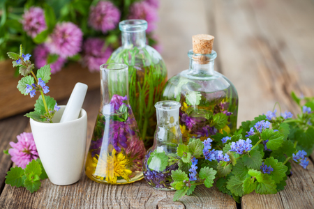 Foto de Bottles of tincture or infusion of healthy herbs, mortar and healing plants on old wooden board. Herbal medicine. - Imagen libre de derechos