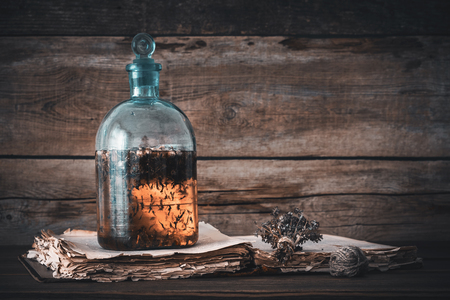 Photo for Tincture or potion bottle, old book and bunch of dry healthy herbs. Herbal medicine. Retro styled. - Royalty Free Image