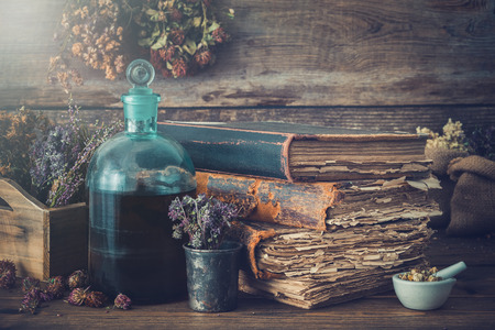 Photo pour Tincture bottles, assortment of dry healthy herbs, old books, mortar, curative drugs. Herbal medicine. Retro styled.  - image libre de droit