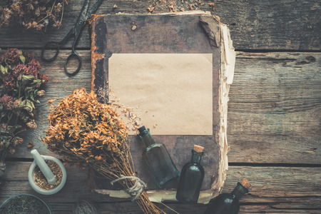 Foto de Tincture bottles, assortment of dry healthy herbs, old books, mortar, scissors. Herbal medicine. Retro styled. Top view, flat lay. - Imagen libre de derechos